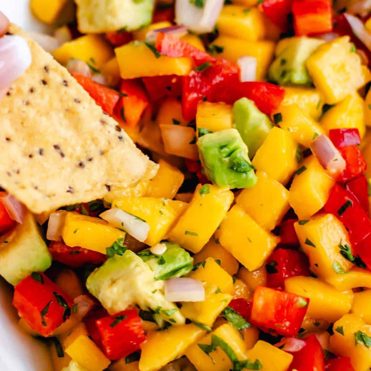 A chip scooping homemade mango and avocado salsa.