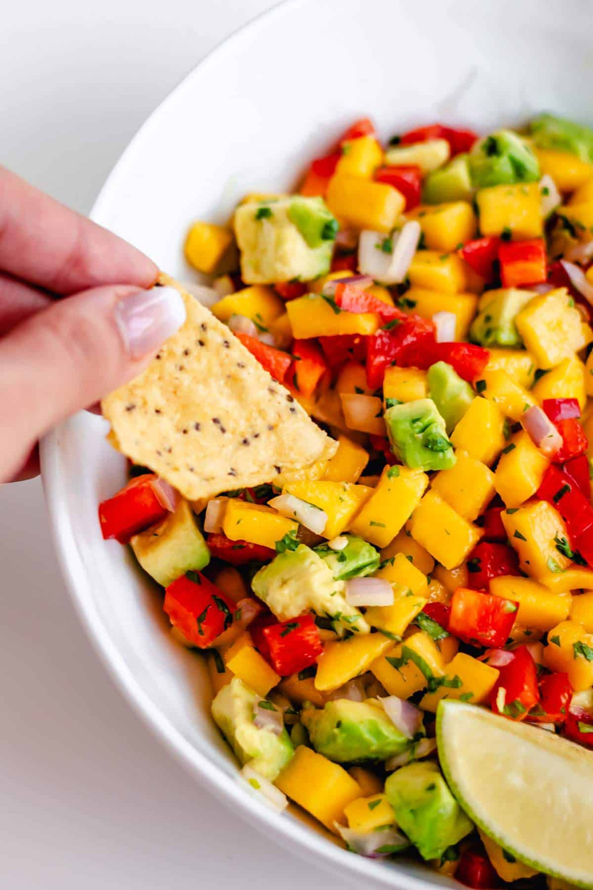 A chip scooping mango and avocado salsa out of a bowl.