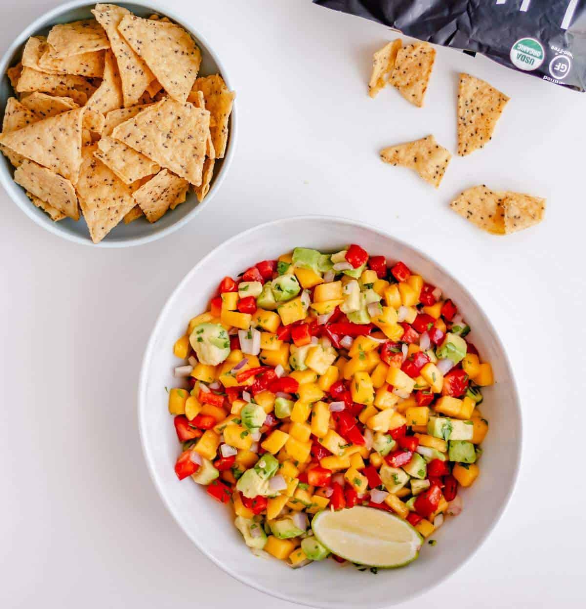 A bowl of mango salsa next to a bowl of chips.