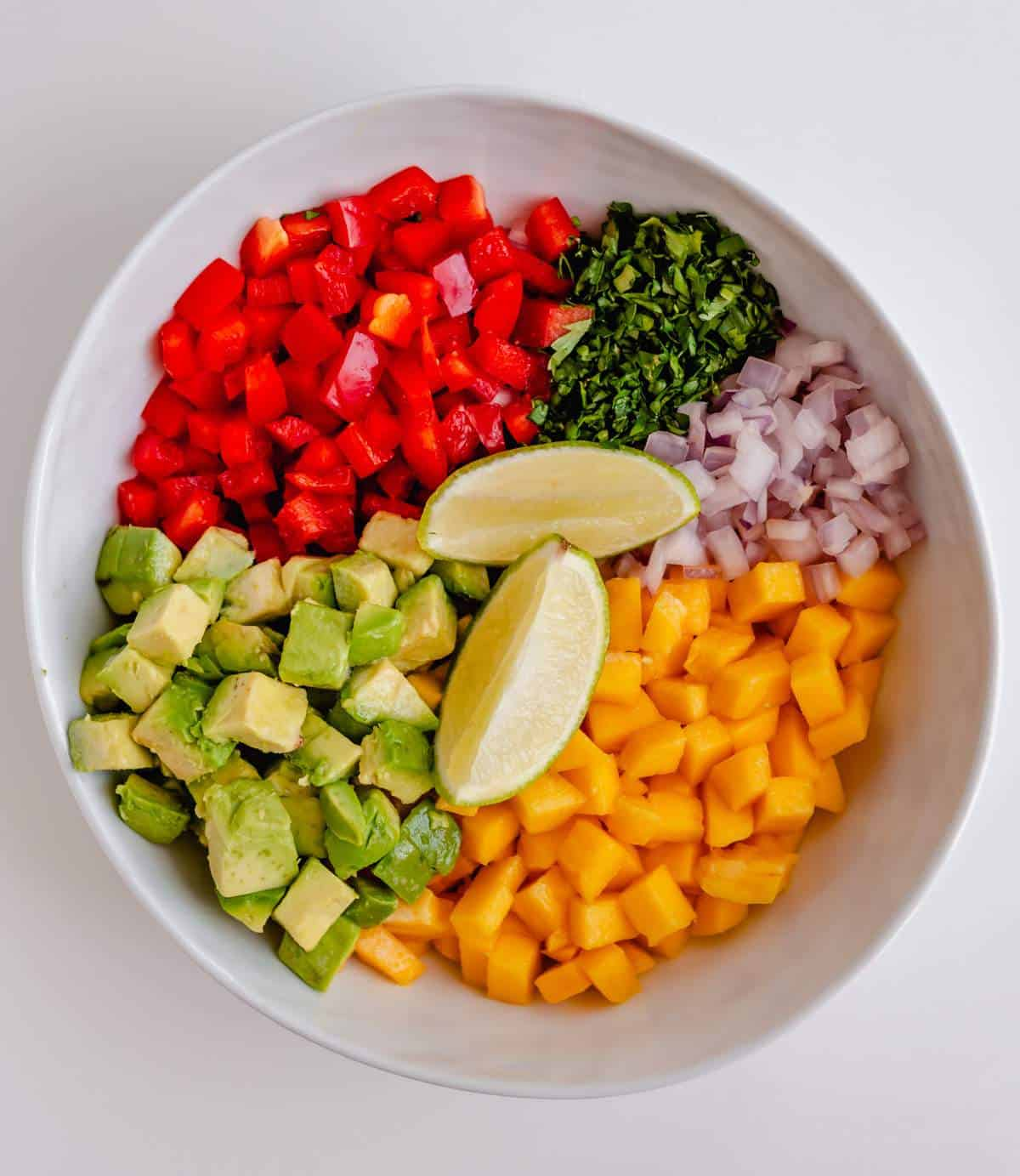 The ingredients in of a bowl of mango and avocado salsa, unmixed.